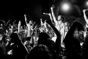 A black-and-white photo of a group of musicians holding up their right fists while a standing audience does the same