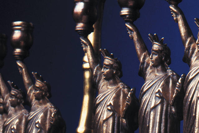 Detail of hanukkah lamp with Statue of Liberty candle holders
