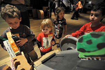 Children helping load animal sculptures onto a conveyer belt up to the ark