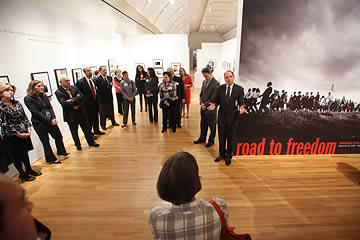 Group of people standing listening to a man talking at the Road to Freedom exhibition