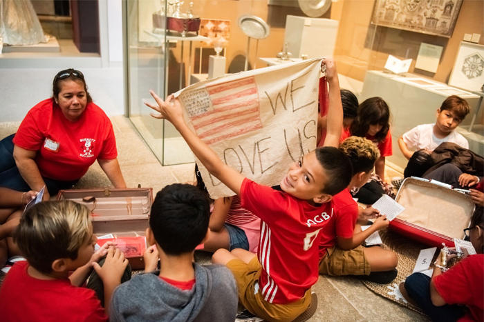 """Student holds up a """"We Love USA"""" banner from a suitcase during the Grade 5 Americans and Their Family Stories school tour"""